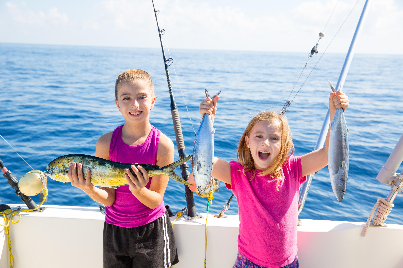 Happy tuna fisherwomen kid girls on boat with fishes trolling catch with dorado Mahi